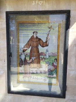 Esta imagen presenta a Junípero Serra como una suerte de 'gigante' por encima de las demás personas. Por cierto ¿por qué tiene una piedra en su mano derecha?